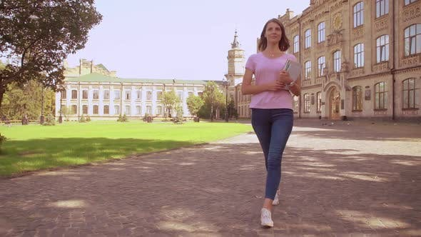 Thumbnail for Woman with Notebook Walks in Campus Area