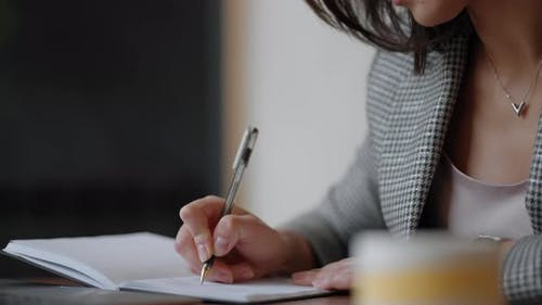 Business Woman Writing Something in Notebook