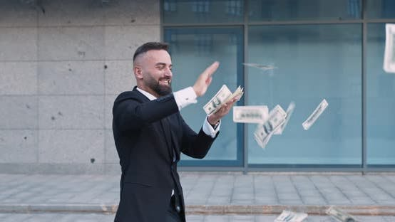 Thumbnail for Happy Middle Aged Businessman Throwing Out Dollar Banknotes, Walking Near Office Building Outdoors