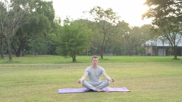 Thumbnail for Young Happy Man Meditating with Eyes Closed at the Park