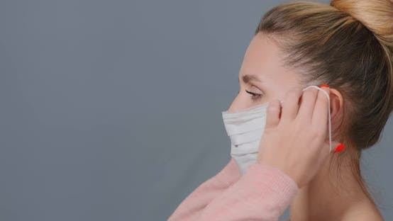 Thumbnail for Junge Frau setzt weiße Einweg-Maske auf Gesicht und Fixes