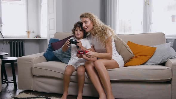 Thumbnail for Boy Are Sitting on a Couch in Light Living Room and Playing Online Video Games