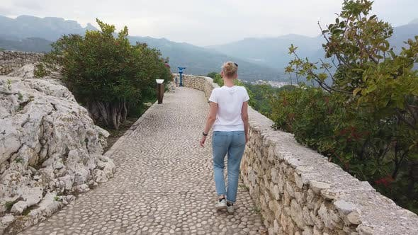 Thumbnail for Blonde Girl Walks on Defensive Walls of Medieval Castle in Europe Mountains