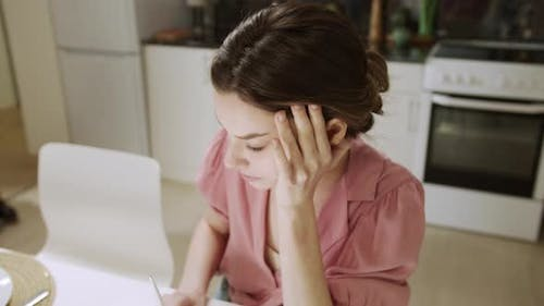 An Adult Woman is Working at Home and Looking Through Documents