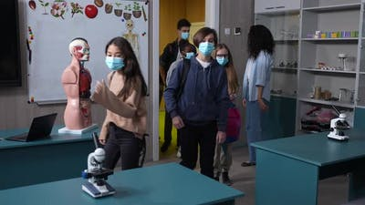 Masked Multinational Pupils Entering Classroom