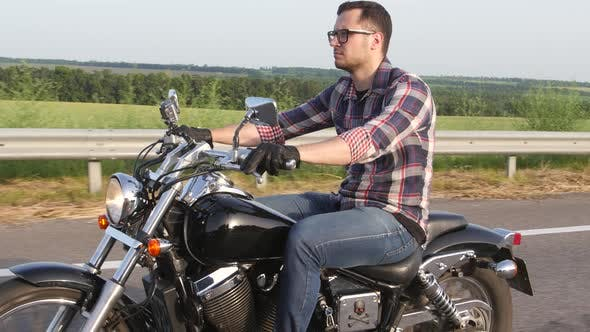 Thumbnail for Serious Man with Glasses on a Motorcycle. Overhead Shot