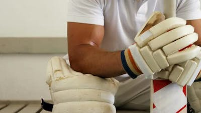 Cricket player sitting on bench in dressing room