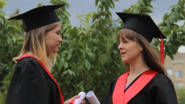 Cover Image for Best Female Friends in Academic Dresses Holding Diplomas and Chatting in Park