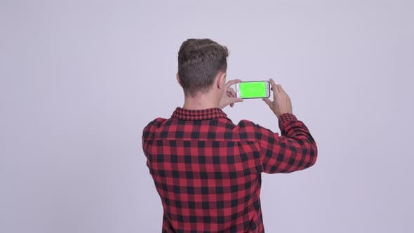 Thumbnail for Rear View of Hipster Man Taking Picture with Phone