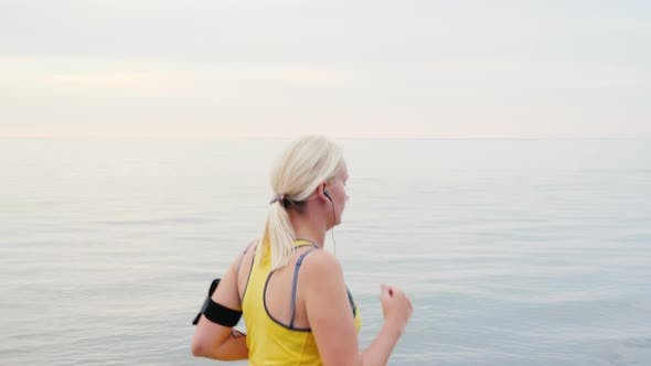 Thumbnail for Young Woman Jogging on the Background of the Sea or Lake