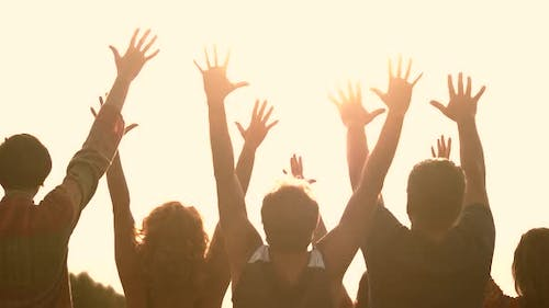 Silhouettes of People with Raised Hands at Sunset