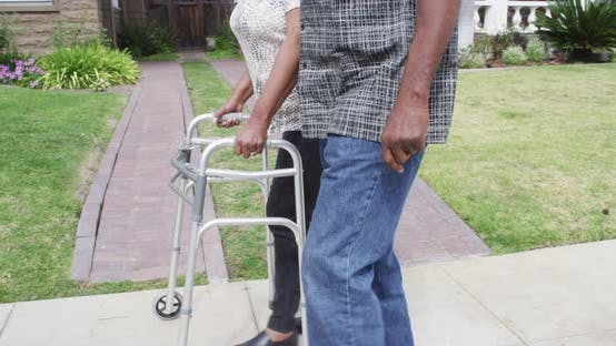 Thumbnail for Mature African couple walking together with walker