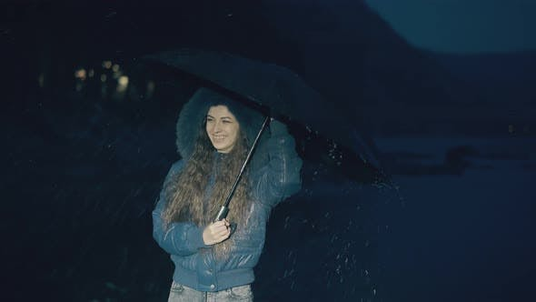 Thumbnail for Happy Girl Jumps Holding Umbrella Under Spring Rain at Night