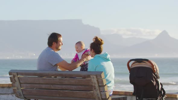 Happy Family Walks Near Ocean in the Sun at Sunset