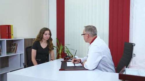 Doctor talking to patient in office. Senior male professional physician consulting female patient