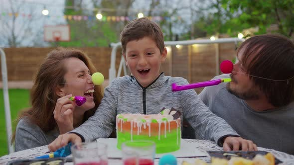 Thumbnail for Happy Little Boy with Parents Blowing Birthday Candles. Parents Dip a Child Face in a Cake.