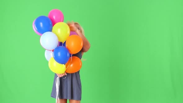 Thumbnail for Young woman peeking behind colorful helium balloons