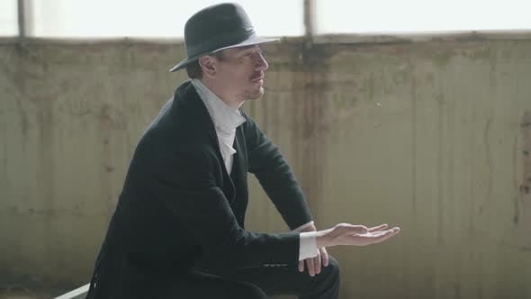 Thumbnail for Handsome Confident Man in a Hat Throws Up and Catches the Coin Sitting in an Abandoned Building. The