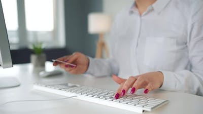 Woman Typing Credit Card Number on Computer Keyboard
