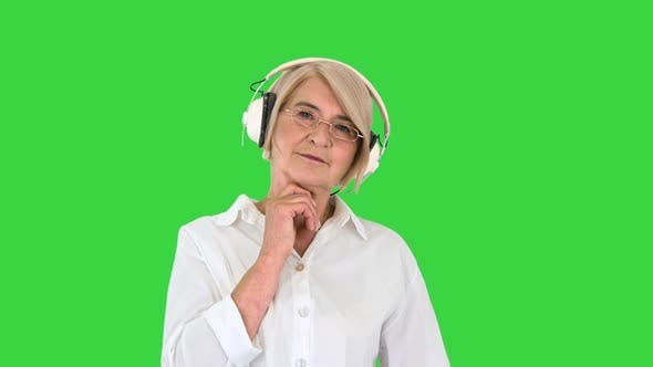 Thumbnail for Old Intelligent Woman Listening To Music in Headphones on a Green Screen, Chroma Key.