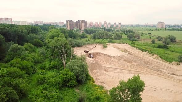 Thumbnail for Top Down View of Excavator Pours Sand Into the Truck, Near the Trees and City Building