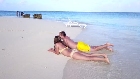 Romantic boy and girl in love dating on vacation spend quality time on beach on summer white sandy b