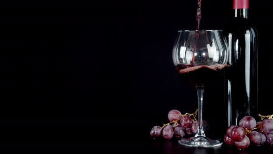 Red Wine Pours Into a Glass with Air Bubbles. On a Black Background