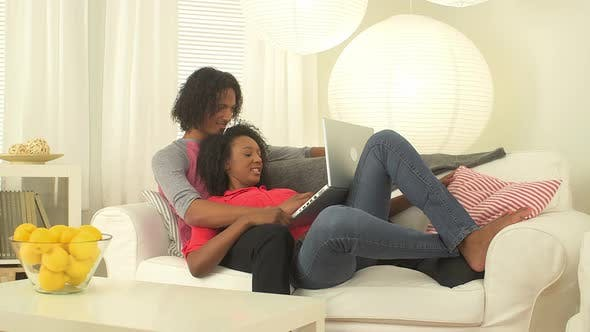 Thumbnail for Black couple using a laptop on couch