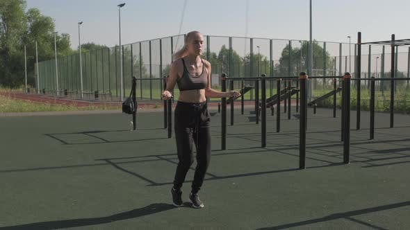 Female Athlete Skipping Rope At Sports Ground