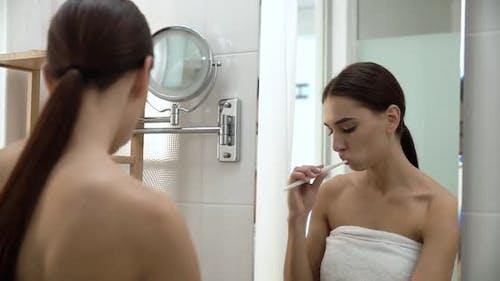 Dental Health. Woman Brushing Teeth In Bathroom