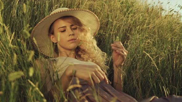 Thumbnail for Girl with a Spike in Her Hands Lies in the Grass