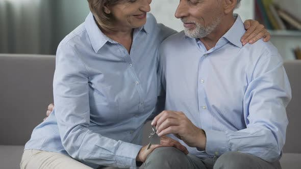 Cover Image for Elderly Male and Female on Couch Holding House-Shaped Key Ring, Real Estate