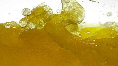 Vegetable Black Cumin Oil Mixed with Sunflower on White Background. Golden Hue of Liquid Oil. Oil Is