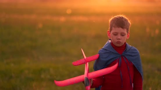 Thumbnail for The Boy Runs Across the Field with a Plane in His Hands at Sunset