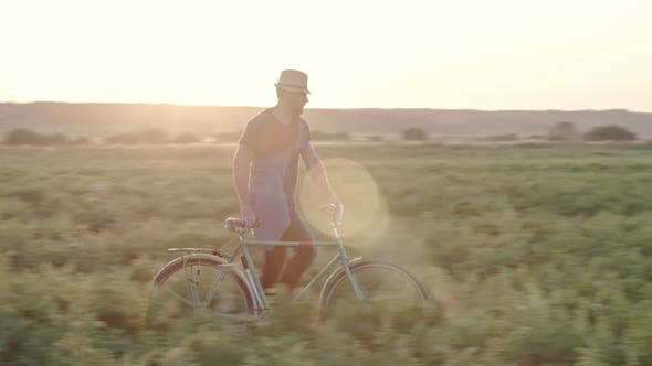 Thumbnail for Man with Bicycle Walking through Grass