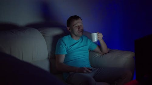 A man with a mug of hot tea sits at the TV late in the evening