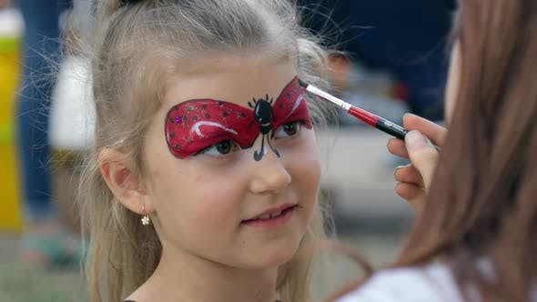 Cute  child girl getting face painted at the festival