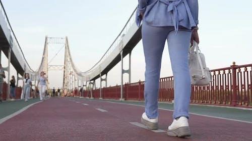 Business Girl Walking on a Foot Bridge
