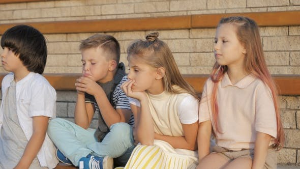 Tired and exhausted primary school kids sitting outdoors.