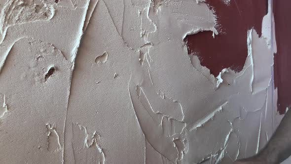 Hand of worker plastering concrete wall with a trowel. Interior finishing works