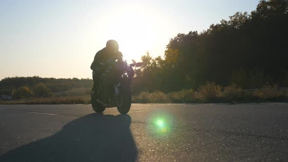 Thumbnail for Man in Helmet Riding Fast on Modern Sport Motorbike at Highway with Sun Flare at Background