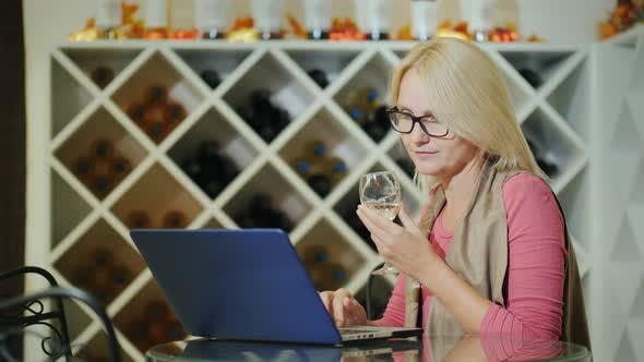 Woman Tasting Wine, Sitting at a Table in a Winery, Using a Laptop