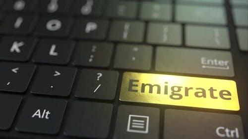 Black Computer Keyboard and Gold Emigrate Key
