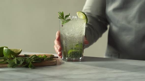 Bartender Prepares a Mojito Cocktail at the Bar