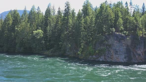 Thumbnail for Aerial Drone Traveling Above Flowing Water Towards Cliff And Shoreline 1