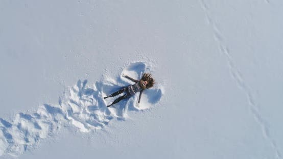Thumbnail for Young Cheerful Woman Is Lying on Snow and Is Making Snow Angels. Aerial Vertical Top-Down View