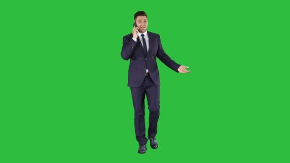Cover Image for Successful man in suit speaks on phone and walks on a Green