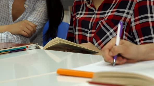 Thumbnail for Männliche Hand schreibt in Notebook in der Bibliothek