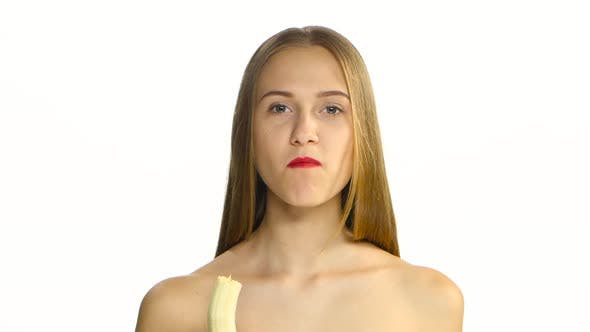 Thumbnail for Girl with Braces and Red Lips Eating a Banana and Looking at the Camera. White. Closeup