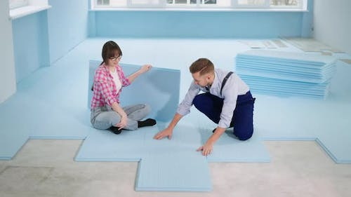 Female and Male Builders Make Floor Thermal Insulation Before Laying Laminate in Room During